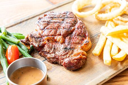medium rare beef steak with vegetable and french fries on board