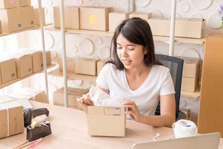 Asian Women business owner working at home with packing box on workplace - online shopping or sell online concept