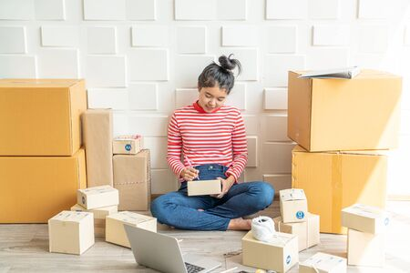 Asian Women business owner working at home with packing box on workplace - online shopping SME entrepreneur or online selling concept Banco de Imagens - 124985051