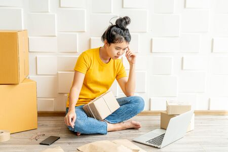 young Asian woman feeling stress or depress in front of her laptop - online selling concept