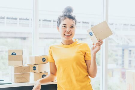 Asian Women business owner working at home with packing box on workplace - online shopping SME entrepreneur or freelance working concept Imagens