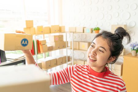 Asian Women business owner working at home with packing box on workplace - online shopping SME entrepreneur or online selling concept Imagens