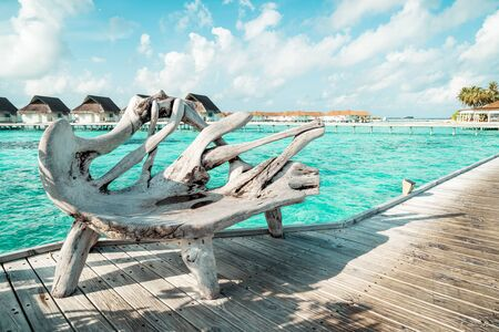 wood bench with tropical Maldives resort hotel and island for holiday vacation concept - boost up color processing style Stockfoto