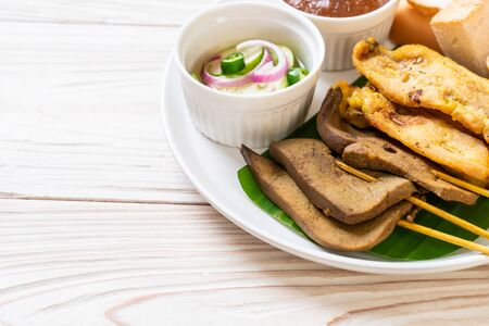 Pork Satay and Liver Satay with Bread and Peanut Sauce  and pickles which are cucumber slices and onions in vinegar - Asian food style Banco de Imagens