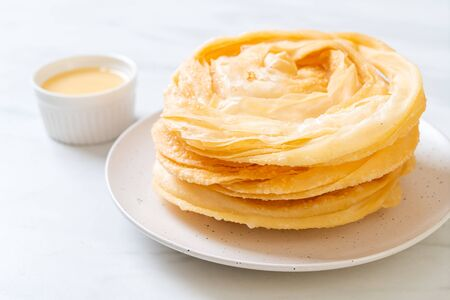 fried crispy roti dough with sweetened condensed milk Stock Photo