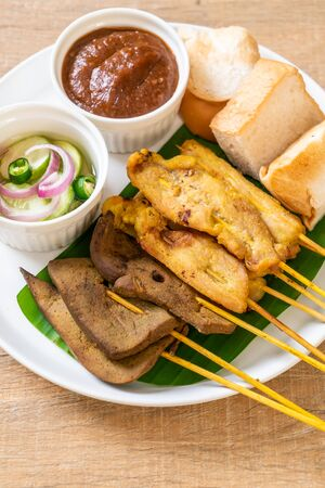 Pork Satay and Liver Satay with Bread and Peanut Sauce  and pickles which are cucumber slices and onions in vinegar - Asian food style Reklamní fotografie