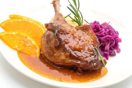 roasted duck leg steak with orange sauce isolated on white background