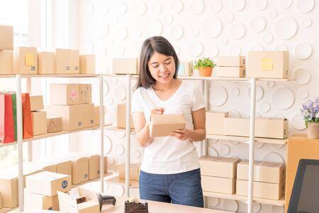 Femme asiatique propriétaire d'entreprise travaillant à la maison avec une boîte d'emballage sur le lieu de travail - entrepreneur de PME d'achat en ligne ou concept de travail indépendant