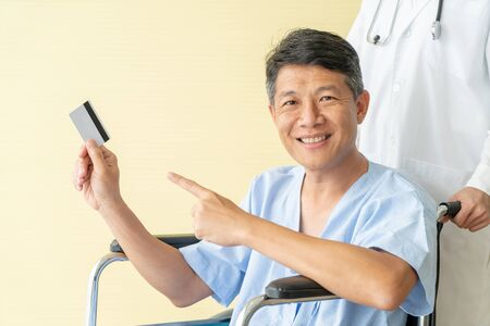 Asian senior patient sitting on wheelchair smiling with holding credit card, selective focus