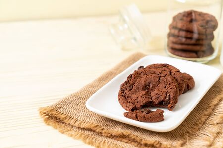 chocolate cookies with chocolate chips on wood background