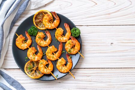 Grilled tiger shrimps skewers with lemon - seafood style