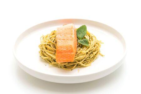 pasta spaghetti with pesto green and salmon isolated on white background