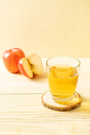 Apple juice with red apples fruit on wood
