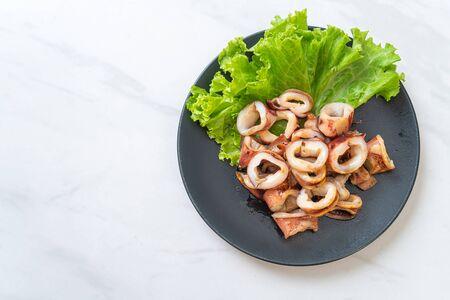 grilled squid on black plate Foto de archivo - 129246887