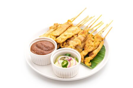Pork satay - Grilled pork served with peanut sauce or sweet and sour sauce - isolated on white background Foto de archivo - 129246055