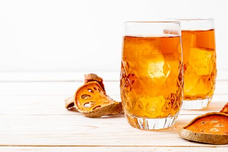 Bael Fruit Herbal Drink Glass on Wood Background