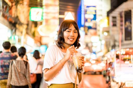 Happy Young Asian Woman Traveler with view at China Town in Bangkok, Thailand
