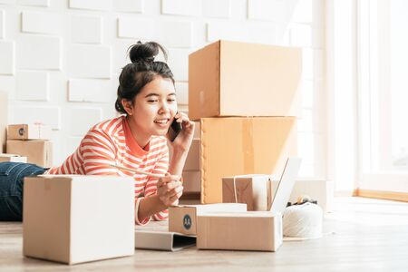 Asian Women business owner working at home with packing box on workplace - online shopping SME entrepreneur or online selling concept Фото со стока