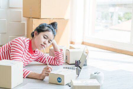 Asian Women business owner working at home with packing box on workplace - online shopping SME entrepreneur or online selling concept Stok Fotoğraf