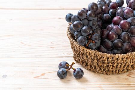 fresh black grapes in basket 스톡 콘텐츠
