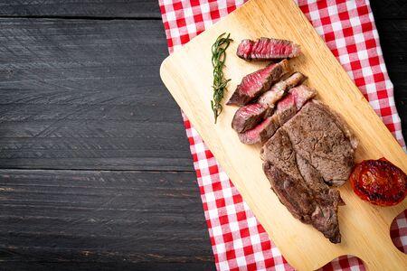 Grilled medium rare beef steak on wood board