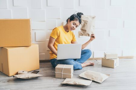 Young asian business start up online seller owner using computer for checking the customer orders from email or website and preparing packages  - online shopping or sell online concept 版權商用圖片