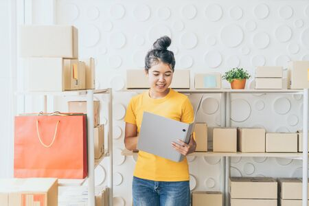 young Asian woman  checking goods on stock shelf at warehouse - online selling or shopping online concept