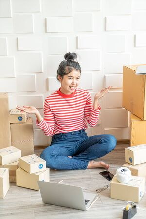 Asian Women business owner working at home with packing box on workplace - online shopping SME entrepreneur or online selling concept 版權商用圖片