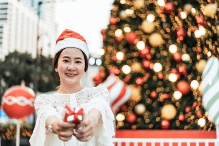 portrait of smiling beautiful young Asian woman with gift on the festive Christmas fair - vintage effect filter