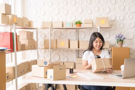 Asian Women business owner working at home with packing box on workplace - online shopping SME entrepreneur or freelance working concept 版權商用圖片