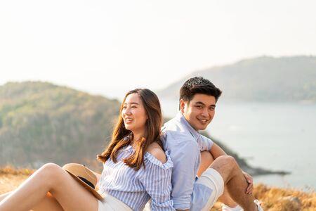 Feliz pareja de jóvenes asiáticos enamorados pasando un buen rato en el parque con el fondo del mar Foto de archivo