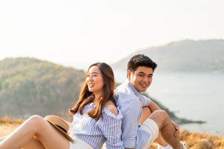 Happy young Asian couple in love having a good time in Park with sea background Stockfoto