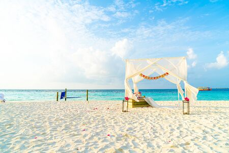 wedding arch on beach with tropical Maldives resort and sea background - vintage effect filter Фото со стока