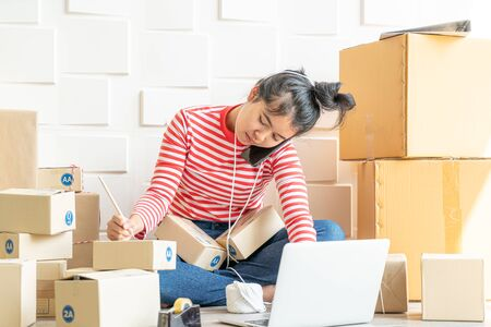 Asian Women business owner working at home with packing box on workplace - online shopping SME entrepreneur or online selling concept Stock Photo