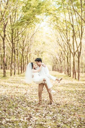 Happy Asian couple in love with tree arch at park Stock Photo
