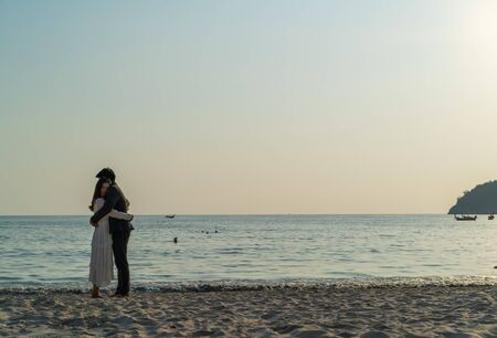 Happy Asian couple going honeymoon travel on tropical sand beach in summer Stock Photo