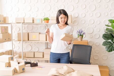 Asian Women business owner working at home with packing box on workplace - online shopping SME entrepreneur or freelance working concept Stok Fotoğraf