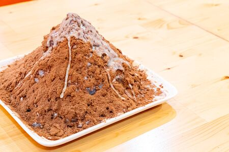 ice shave with chocolate powder and sweetened condensed milk on wood plate 免版税图像