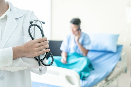 female doctor holding stethoscope with patient background Stock Photo