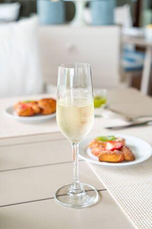 Copa de vino espumoso en la mesa de la cafetería restaurante - punto de enfoque selectivo
