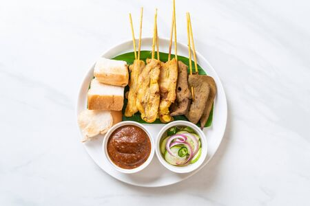 Pork Satay and Liver Satay with Bread and Peanut Sauce  and pickles which are cucumber slices and onions in vinegar - Asian food style Stockfoto