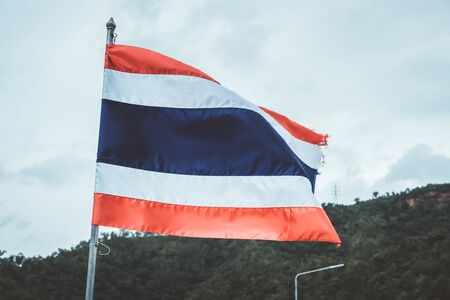 National flag of Thailand with cloudy sky background