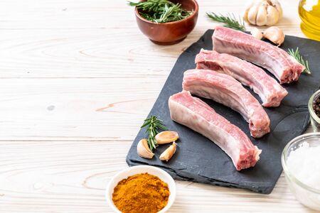 Fresh raw pork ribs with ingredients on black board