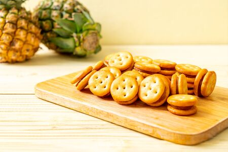 biscuits with pineapple jam on wood background