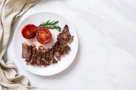 Grilled medium rare beef steak with tomatoes Imagens