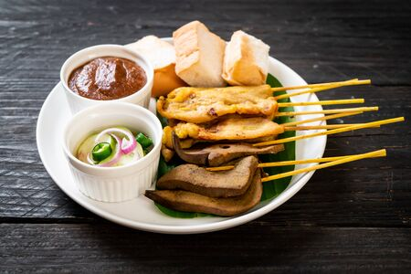 Pork Satay and Liver Satay with Bread and Peanut Sauce  and pickles which are cucumber slices and onions in vinegar - Asian food style Фото со стока