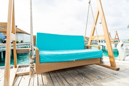 empty sofa swing with tropical Maldives resort and sea background - vintage effect filter
