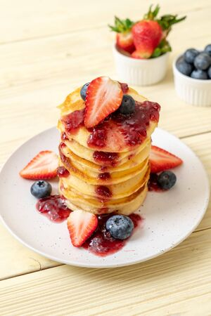 pancake with strawberries, blueberries and berry sauce
