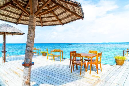 empty outdoor wood table and chair with sea view background in Maldives Banco de Imagens