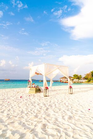 wedding arch on beach with tropical Maldives resort and sea background - vintage effect filter Stock Photo